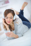 Beautiful young woman listening to music in bed Royalty Free Stock Photo
