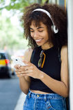 Beautiful young woman listening to music in city. Royalty Free Stock Images