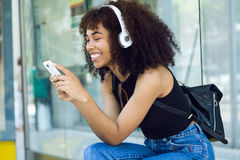 Beautiful young woman listening to music in city. Stock Photo