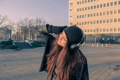 Beautiful young woman listening to music in the city streets Stock Photography