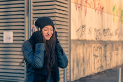 Beautiful young woman listening to music in the city streets Royalty Free Stock Photos