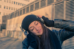 Beautiful young woman listening to music in the city streets Royalty Free Stock Image