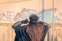 Beautiful young woman listening to music in the city streets Stock Photos