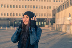 Beautiful young woman listening to music in the city streets Royalty Free Stock Images
