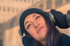Beautiful young woman listening to music in the city streets Stock Photo