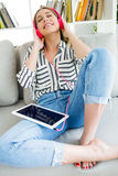 Beautiful young woman listening to music with digital tablet. Stock Image