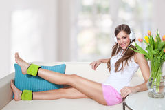 Beautiful young woman listening to music while doi. Ng leg exercis at home Royalty Free Stock Photos