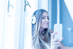 Beautiful young woman listening to Music on Headphones Stock Photo