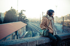 Beautiful young woman listening to music headphones. In the city winter Stock Photos
