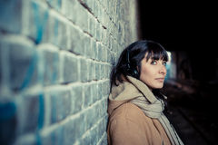 Beautiful young woman listening to music headphones. In the city winter Stock Photography