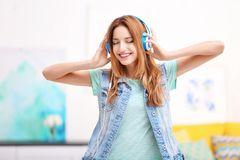 Beautiful young woman listening to music. In headphones at home Stock Photo
