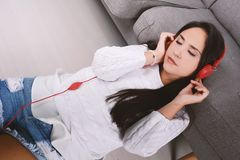 Woman listening music. Beautiful young woman listening to music with headphones and relaxed. Indoors Stock Images