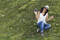 Beautiful young woman listening to music on her smart phone. She Stock Photos