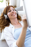 Beautiful young woman listening to music at home. Royalty Free Stock Images
