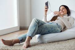 Beautiful young woman listening to music with mobile phone at ho Royalty Free Stock Photography
