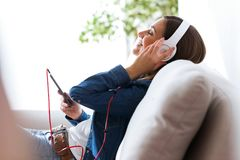 Beautiful young woman listening to music with mobile phone at home. Portrait of beautiful young woman listening to music with mobile phone at home Royalty Free Stock Image
