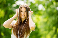 Beautiful young woman listening to music in a park Stock Images