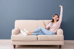Beautiful young woman listening to music on sofa,. Indoors Stock Photography