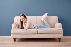 Beautiful young woman listening to music on sofa. Indoors Stock Images