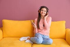 Beautiful young woman listening to music on sofa. Indoors Stock Image