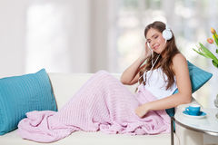 Beautiful young woman listening to music on the sofa Stock Image