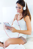 Beautiful young woman listening to music with tablet sitting on Royalty Free Stock Photos