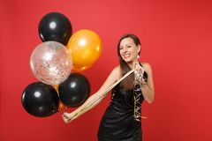 Beautiful young woman in little black dress celebrating holding air balloons isolated on red background. St. Valentine`s stock image