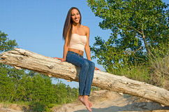 Beautiful young woman on a log Royalty Free Stock Image