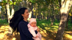 Young woman with long hair playing with baby stock footage