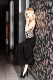 Beautiful young woman in a long black skirt posing near the wall Royalty Free Stock Photos
