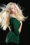Beautiful young woman with long blond hair. On black background royalty free stock photo