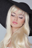 Beautiful young woman with long blond hair wearing in hat. Prett Royalty Free Stock Photography