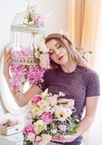 Beautiful young woman with long blonde hair, blue eyes, flowering cage, wearing t-shirt. Stock Images
