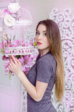 Beautiful young woman with long blonde hair, blue eyes, flowering cage, wearing t-shirt. Spring mood in pink rose warm tones Stock Image