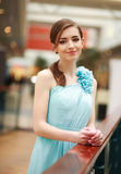 Beautiful young woman in a long blue dress indoor Royalty Free Stock Photos