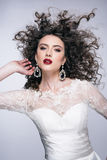 Beautiful young woman with long brown hair, red lips,jewellery in wedding dress Pretty model poses at studio. Royalty Free Stock Photo