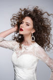 Beautiful young woman with long brown hair, red lips,jewellery in wedding dress Pretty model poses at studio. Stock Image