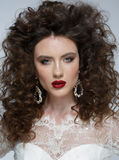Beautiful young woman with long brown hair, red lips,jewellery in wedding dress Pretty model poses at studio. Royalty Free Stock Photography