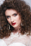 Beautiful young woman with long brown hair, red lips,jewellery in wedding dress Pretty model poses at studio. Stock Photos