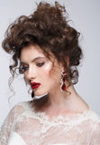 Beautiful young woman with long brown hair, red lips,jewellery in wedding dress Pretty model poses at studio. Stock Images