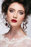 Beautiful young woman with long brown hair, red lips,jewellery in wedding dress Pretty model poses at studio. Royalty Free Stock Images