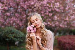 Beautiful young woman with long curly blonde hair and closed eyes holding blooming branch of sakura tree stock photo