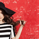 Beautiful young woman with long curly hair in black hat and striped dress on red background. Royalty Free Stock Photography
