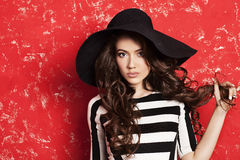 Beautiful young woman with long curly hair in black hat and striped dress on red background. Black and white stripes. Stylish fashion model. Face close up. Big Royalty Free Stock Images