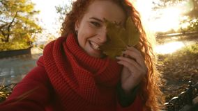 Beautiful young woman with long curly hair closed eye with autumn leaf. Girl smiling at camera and posing. Outdoor stock footage