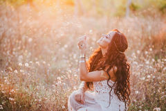 Beautiful young woman with long curly hair dressed in boho style dress posing in a field with dandelions. Sunset Stock Images