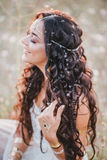 Beautiful young woman with long curly hair dressed in boho style dress posing in a field with dandelions royalty free stock photography
