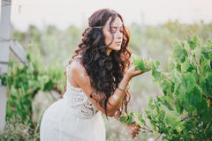 Beautiful young woman with long curly hair dressed in boho style dress posing in a field with dandelions Royalty Free Stock Images