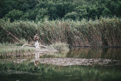 Beautiful young woman with long curly hair dressed in boho style dress posing near lake. Summer mood Royalty Free Stock Photography