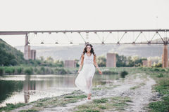 Beautiful young woman with long curly hair dressed in boho style dress posing near lake. Summer mood Stock Photography